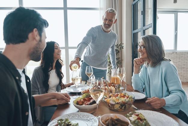 Felice uomo anziano che beve vino e sorride mentre cena con la famiglia