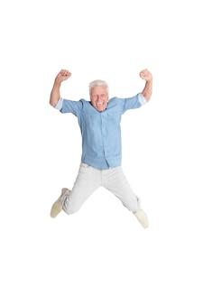 Uomo anziano felice in camicia che salta con le mani in alto su sfondo bianco