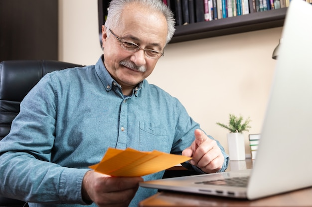 Uomo maggiore felice che lavora con il computer portatile a casa passando in rassegna bollette e documenti. lavoro a casa.
