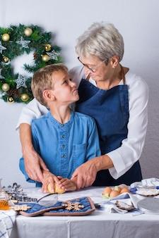 Felice donna matura anziana, nonna e ragazzo, nipote che cucina, impasta la pasta, cuoce la torta, la torta, i biscotti. tempo in famiglia nell'accogliente cucina. attività natalizie invernali stagionali a casa.