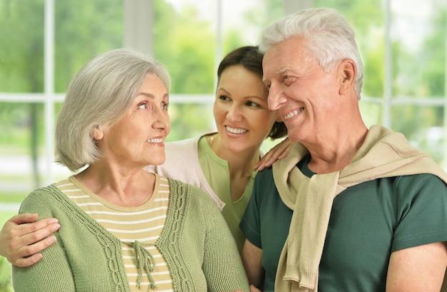 Genitori anziani felici con la figlia sullo sfondo