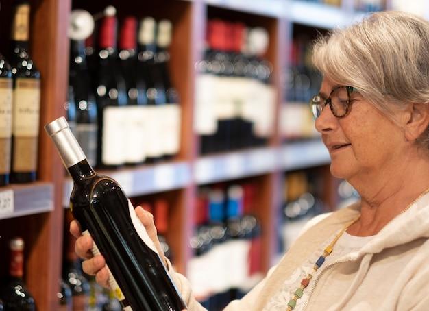 La donna anziana felice che sceglie una bottiglia di vino rosso nel negozio. il concetto di consumismo