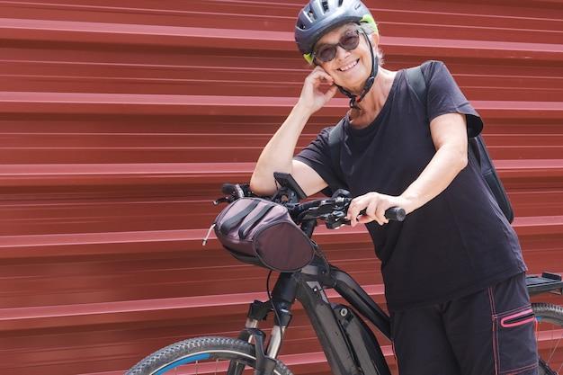 Felice ciclista donna anziana in un'escursione all'aperto vicino al pannello di metallo rosso che si gode uno stile di vita sano