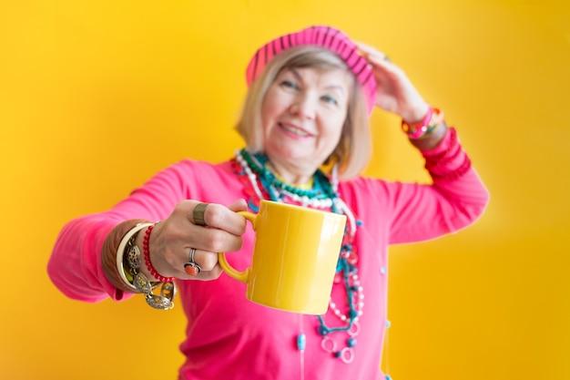 Felice donna anziana faccia buffa che beve una tazza di caffè o tè in abiti eleganti