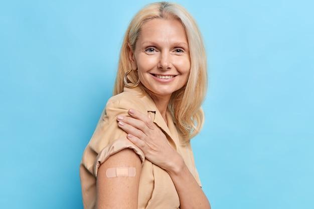 Una donna anziana felice ottiene un vaccino efficace contro il coronavirus contro la nuova variante delta mostra un braccio con cerotto adesivo sul luogo dell'inoculazione è stata vaccinata per proteggere la salute e ottenere il passaporto covid