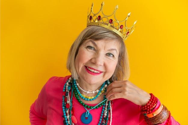 Felice donna anziana che si diverte indossando abiti eleganti. ritratto di nonna. concetti sulle persone anziane su sfondi colorati