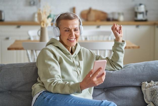 Felice donna anziana in cuffia che ascolta musica sullo smartphone mentre si rilassa a casa sul divano