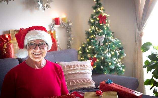 Una donna anziana felice con il cappello di babbo natale sembra sorpresa dal regalo ricevuto per natale
