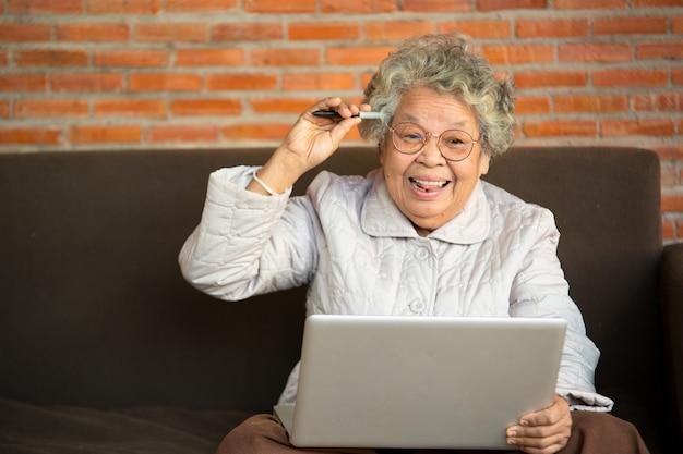 Donna senior felice messa sul sofà nel computer portatile di uso del salone, generazione più anziana facendo uso del concetto moderno di tecnologia.