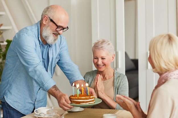 Felice senior donna seduta al tavolo mentre i suoi amici portano la torta di compleanno e si congratulano con lei
