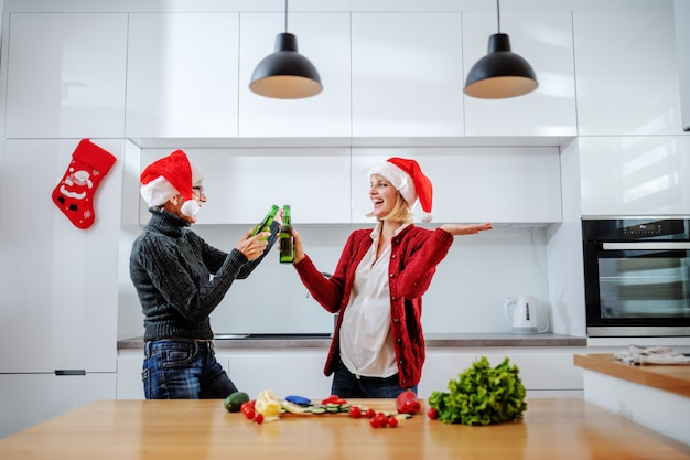 Donna senior felice che tosta con la birra con sua figlia mentre stando nella cucina. entrambi hanno cappelli di babbo natale in testa.