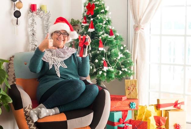 Felice donna anziana che indossa un cappello di babbo natale dopo aver preparato i regali e le decorazioni natalizie riposa con in mano un tablet legato con l'arco - buon natale a casa per il pensionato anziano in attesa della famiglia