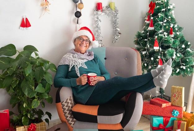 Felice donna anziana che indossa un cappello da babbo natale dopo aver preparato i regali di natale e le decorazioni riposa con in mano una tazza di tè - buon natale a casa per un anziano pensionato in attesa della famiglia