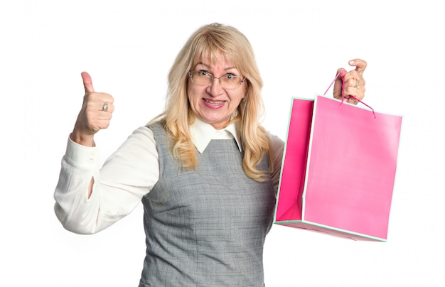 La donna senior felice con una manifestazione rosa del pacchetto sfoglia su su un fondo bianco.