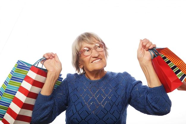 Donna senior felice con i sacchetti della spesa