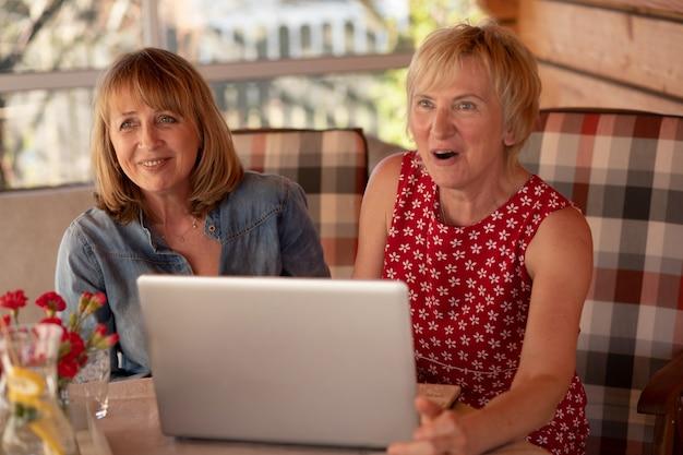 Donne anziane felici che tengono il computer portatile e lavorano insieme a casa