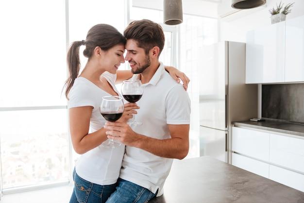 Felice giovane coppia sensuale che abbraccia e beve vino rosso in cucina