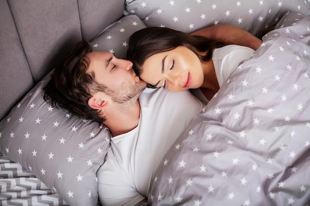 Giovani coppie sensuali felici che si trovano insieme a letto