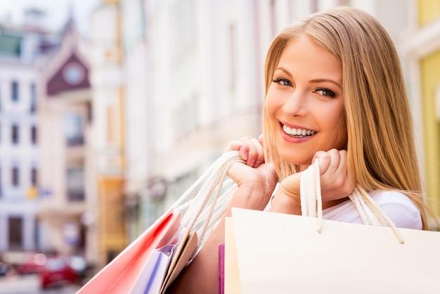 Felice ragazza maniaca dello shopping. bella giovane donna allegra che tiene le borse della spesa e guarda la telecamera mentre sta in piedi all'aperto