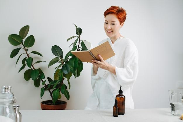 Felice donna dai capelli corti che guarda il taccuino ecologico con una copertina di cartone. girare pagine bianche.