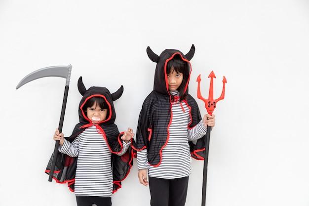 Ragazze di pari livello felici alla festa di halloween. bambini che indossano costumi di halloween. concetto di bambini pronti per una festa.