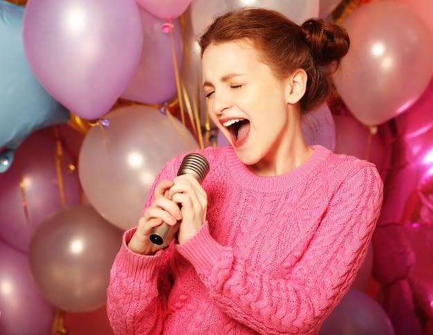 Ragazza di canto felice. redhair bellezza donna con microfono con palloncini rosa.