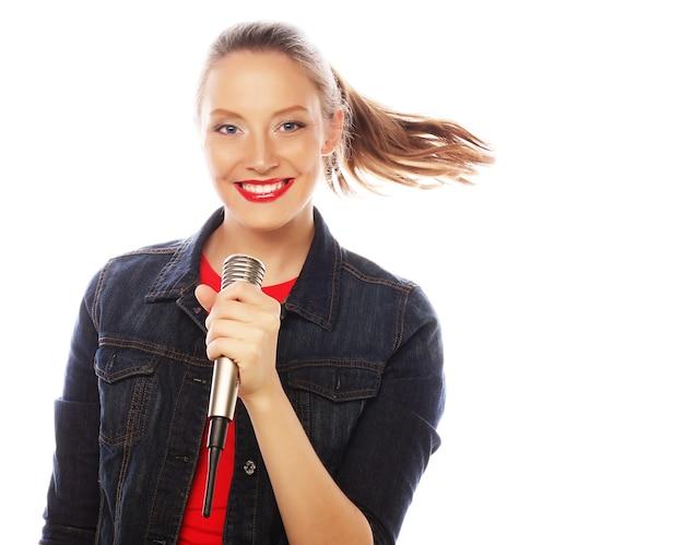 Ragazza felice che canta. donna di bellezza che indossa maglietta rossa con microfono su sfondo bianco.