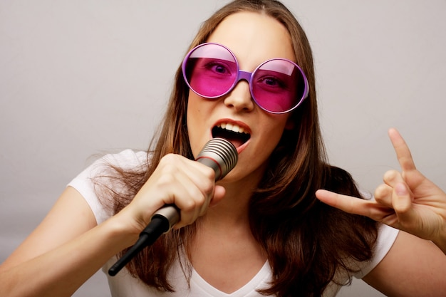 Ragazza felice che canta. donna di bellezza che indossa t-shirt bianca e grandi occhiali da sole con microfono su sfondo bianco. stile ipster