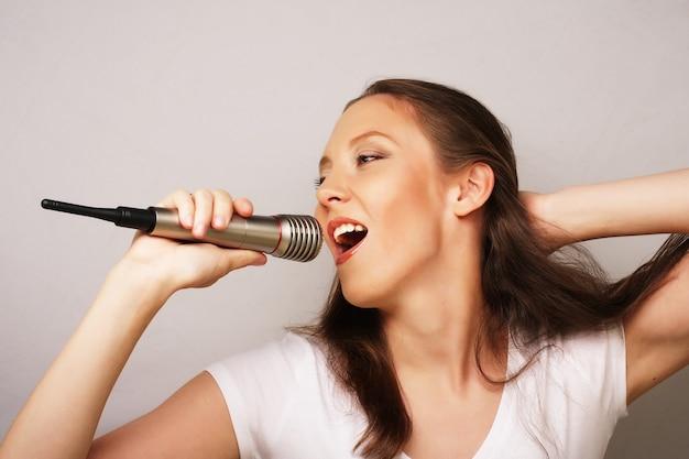 Ragazza felice che canta. donna di bellezza che indossa t-shirt bianca con microfono su sfondo bianco.