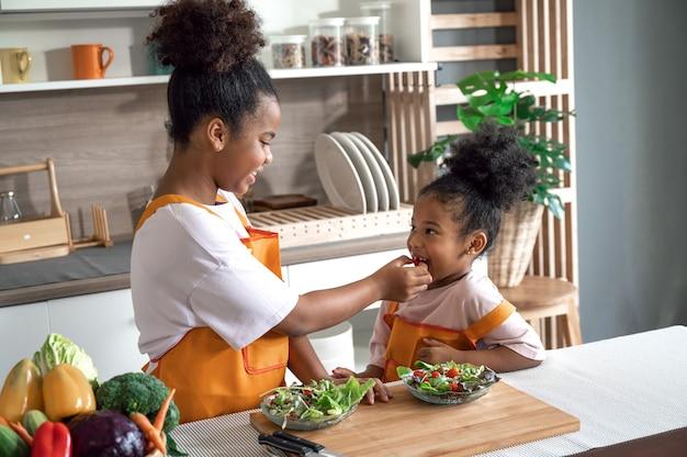 Pelle nera della sorella felice con insalata sulla zolla in cucina