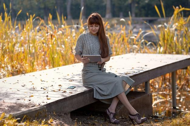 Felice donna seduta nel parco vicino al laghetto con una tavoletta digitale durante le passeggiate autunnali