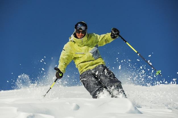 Felice sciatore in abbigliamento sportivo giallo a cavallo lungo il pendio in georgia, gudauri