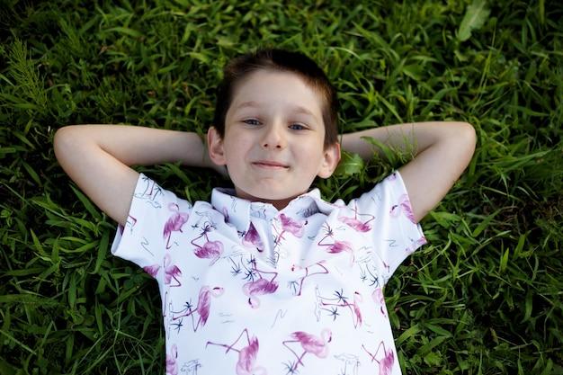 Felice piccolo ragazzo con affascinanti occhi azzurri sdraiato sull'erba verde nel parco.