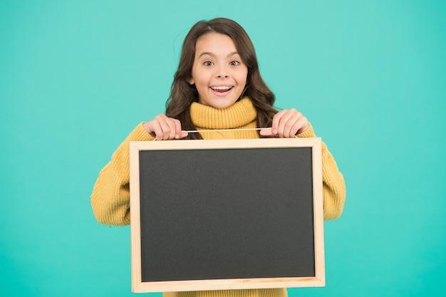 Il piccolo bambino felice fa il gesto della mano presentando il prodotto. grande pubblicità di vendita. miglior prezzo. info utili qui. benvenuto a bordo. felice piccola ragazza tenere lavagna. copia spazio per il tuo annuncio.