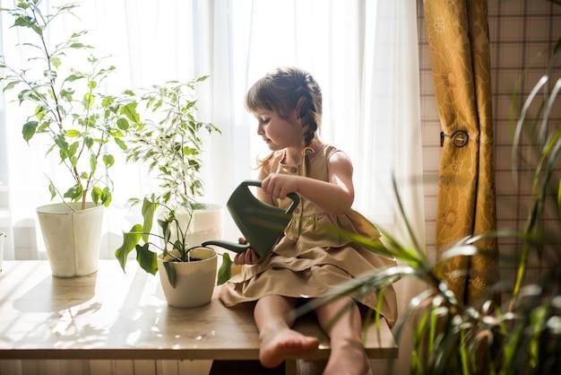 La piccola neonata sveglia felice si prende cura delle piante d'appartamento. ragazza che innaffia e spruzza piante da interno a casa