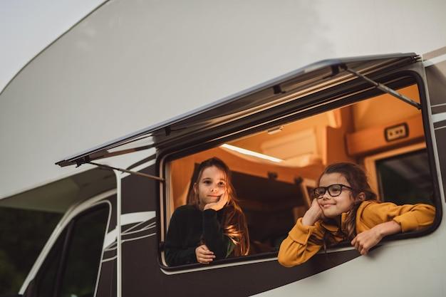 Piccole ragazze felici che guardano fuori dalla finestra della roulotte la sera, un viaggio di vacanza in famiglia.