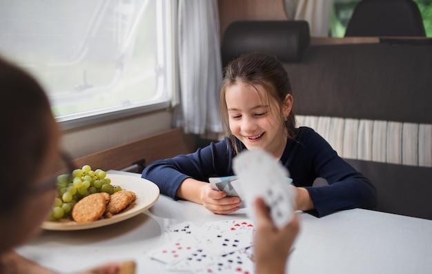 Piccole ragazze felici che giocano a carte al chiuso in roulotte, viaggio di vacanza in famiglia.