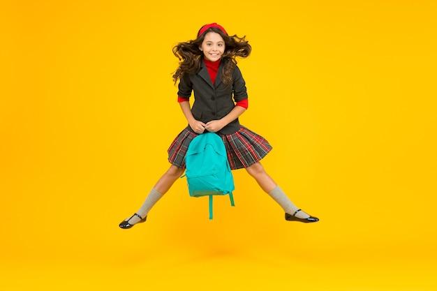 Un ragazzino felice in uniforme formale tiene la borsa della scuola che salta a mezz'aria su sfondo giallo, scolarizzazione.