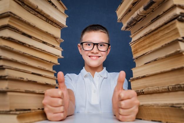 Felice ragazzo intelligente con gli occhiali seduto tra due pile di libri e guarda la fotocamera sorridendo, mostrando i pollici in su.