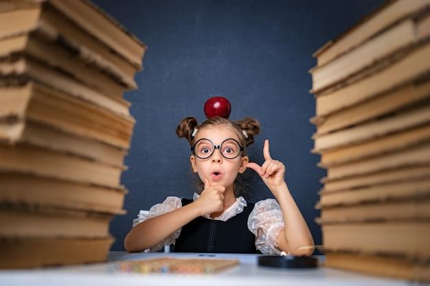 Felice ragazza intelligente in bicchieri arrotondati pensieroso seduto tra due pile di libri con mela rossa sulla testa, puntando il dito verso l'alto