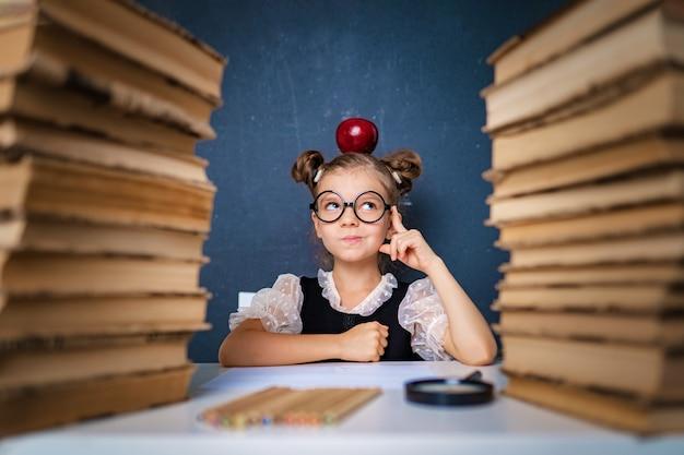 Felice ragazza intelligente in bicchieri arrotondati pensieroso seduto tra due pile di libri con mela rossa sulla testa