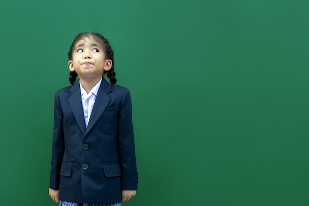 Bambini della scuola asiatica di sorriso felice con l'uniforme formale di affari su fondo verde