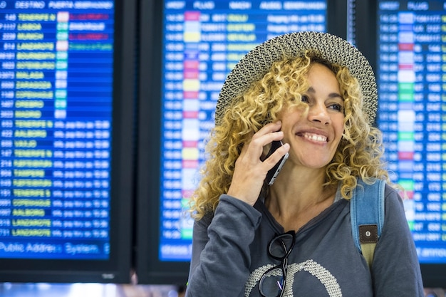 Il sorriso felice e il ritratto allegro della giovane donna fanno una telefonata all'aeroporto durante il viaggio