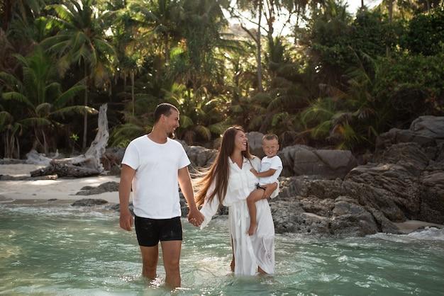 La famiglia europea di sorriso felice riposa e corre sulla spiaggia di sabbia bianca.
