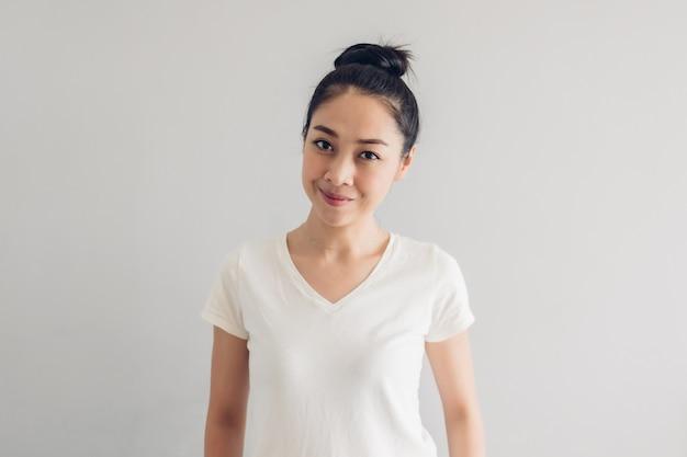 Fronte di sorriso felice della donna in maglietta bianca e sfondo grigio.