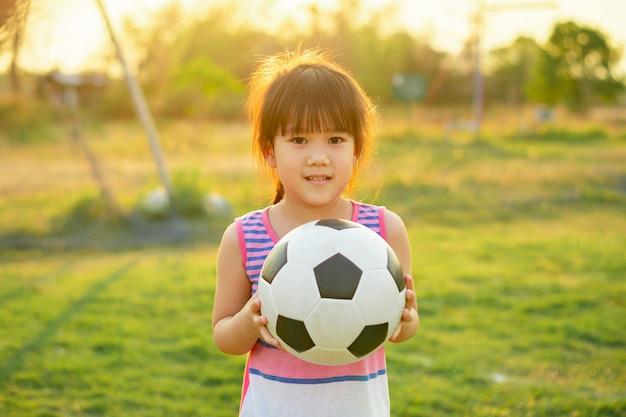 Bambini felici e sorridenti che giocano a calcio calcio per l'esercizio sotto la luce solare.