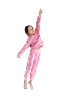 Felice e sorride la piccola ragazza asiatica del bambino in tuta rosa o panno di sport che salta in aria isolata sopra fondo bianco.
