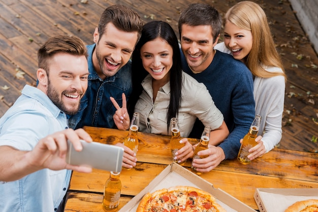 Sorriso felice per selfie! vista dall'alto di un gruppo di giovani che tengono in mano bottiglie di birra e fanno selfie sullo smartphone mentre si trovano all'aperto
