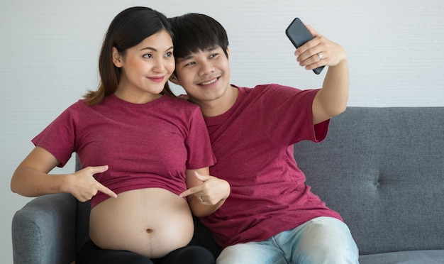 Felice giovane coppia sorridente vestita casualmente seduta su un divano insieme sorridente e facendo un selfie. stanno aspettando un bambino sano. gravidanza e concetto di famiglia.