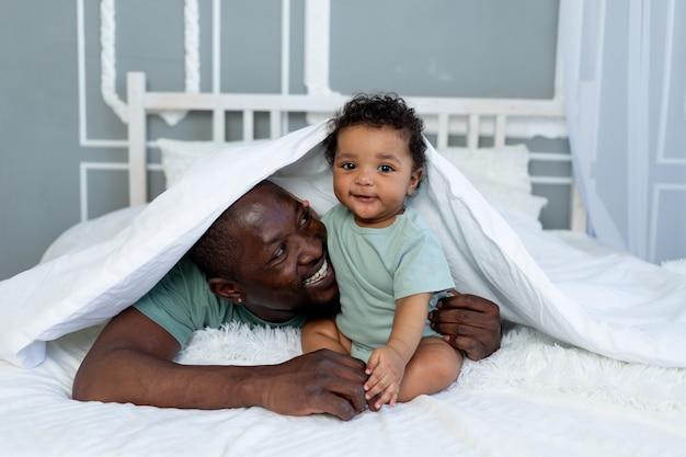 Papà afroamericano sorridente felice con il figlio del bambino sul letto a casa che stringe a sé sotto la coperta, famiglia felice, festa del papà